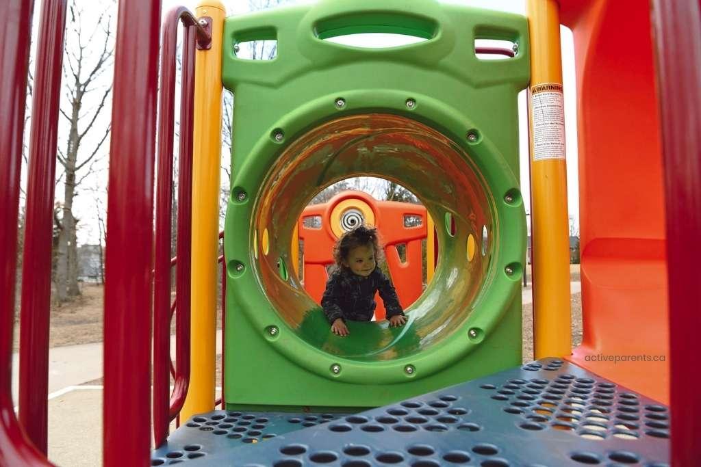 little one climbing through tunnel